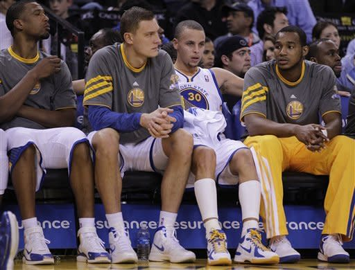 Golden State Warriors' Stephen Curry (30) sits on the bench beside Andris Biedrins, second from left, during the second half of an NBA basketball game against the Memphis Grizzlies Wednesday, March 7, 2012, in Oakland, Calif. (AP Photo/Ben Margot)