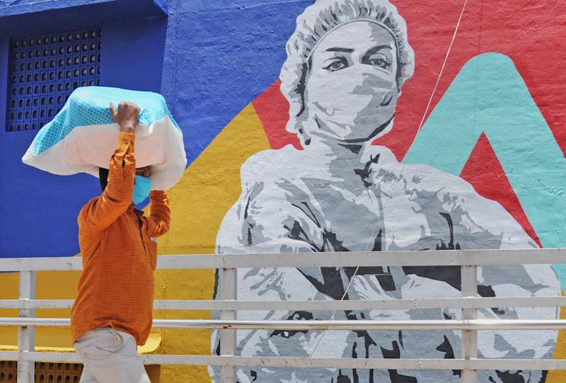 A man carrying a sack on his head walks past a graffiti of coronavirus warrior in Mumbai.Mural depicts a nurse as one of the many corona warriors who have worked throughout the lockdown, exposing themselves to the risk of infection. It is the expression of what every citizen is thankful for the efforts of essential service providers in the face of rising covid-19 cases. (Photo by Ashish Vaishnav/SOPA Images/LightRocket via Getty Images)