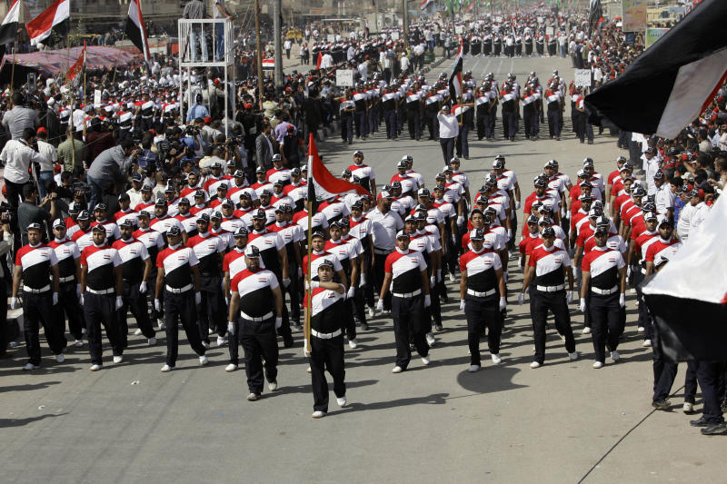 Militiamen loyal to cleric Muqtada al-Sadr march in the Sadr City district of Baghdad, Iraq, Thursday, May 26, 2011. Tens of thousands of followers of the Shiite anti-American cleric are rallying in Baghdad, demanding the U.S. military leave Iraq at the end of the year. (AP Photo/Hadi Mizban)