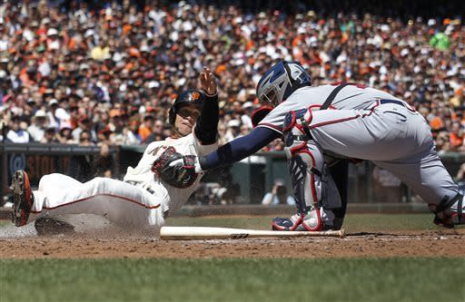 San Francisco Giants' Gregor Blanco, left, is tagged out at home plate by Atlanta Braves catcher Brian McCann during the fourth inning of a baseball game in San Francisco, Sunday, May 12, 2013. (AP Photo/Tony Avelar)
