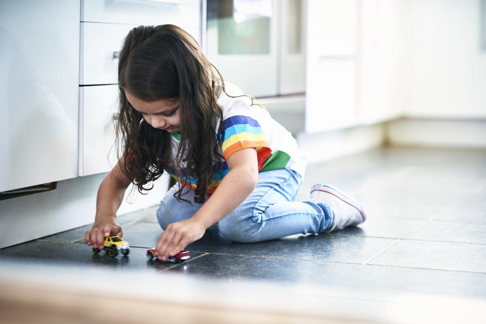 Little girl paying with toy cars