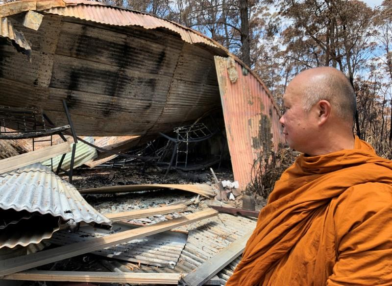 The Abbot of Sunnataram Forest Monastery, Phra Mana, 56, looks at the ruins of a burnt female dormitory in Bundanoon, Australia