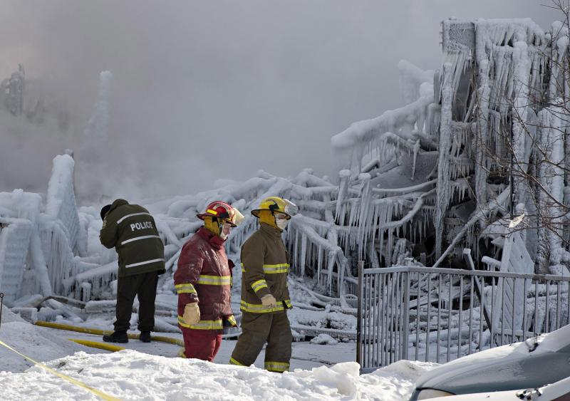 Canadian police and firefighters survey the damage after a fatal fire at a seniors residence in L'Isle-Verte, Quebec, Thursday, Jan. 23, 2014. The fire raged through the seniors' residence, killing at least three people and leaving about 30 unaccounted for. The massive fire in the 52-unit complex broke out around 12:30 a.m. in L'Isle-Verte, about 140 miles (225 kilometers) northeast of Quebec City. (AP Photo/The Canadian Press, Jacques Boissinot)