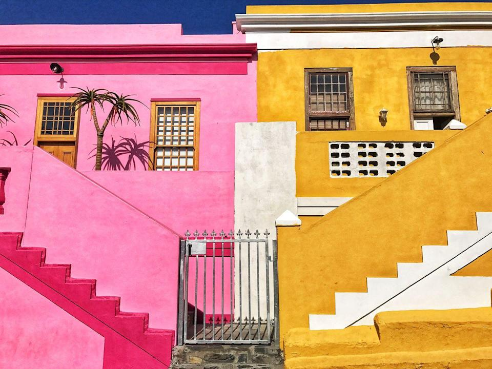 <p>One glance at its neon-colored homes and you know you've made to Cape Town's multicultural hub, the Bo-Kaap neighborhood. The origins of the distinct quarter date back to the 1760s, when rental homes were built for enslaved people from Malaysia, Indonesia, and across Africa by Dutch colonialists. </p><p>At the time, the leases required all houses to be painted white, but once the inhabitants were able to buy and own property, they painted the homes vibrant shades as an expression of freedom. Today, the Bo-Kaap Museum details history of the area and the lives of the Cape Malay people. </p>