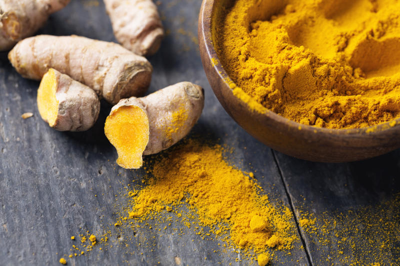 Freh turmeric roots and turmeric powder in a wooden bowl on rustic wood