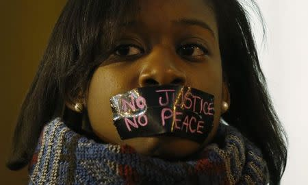 A protester wears tape over her mouth during a silent demonstration against what they say is police brutality after the Ferguson shooting of Michael Brown, an unarmed black teenager, by a white police officer, in St. Louis, Missouri, March 14, 2015. REUTERS/Jim Young
