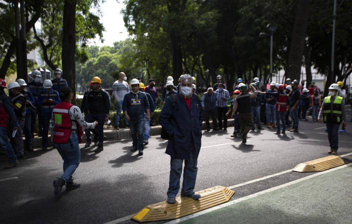 Employees stand outside of their work building after a 7.5 earthquake, in Mexico City, Tuesday, June 23, 2020. The earthquake centered near the resort of Huatulco in southern Mexico swayed buildings Tuesday in Mexico City and sent thousands into the streets.(AP Photo/Fernando Llano)