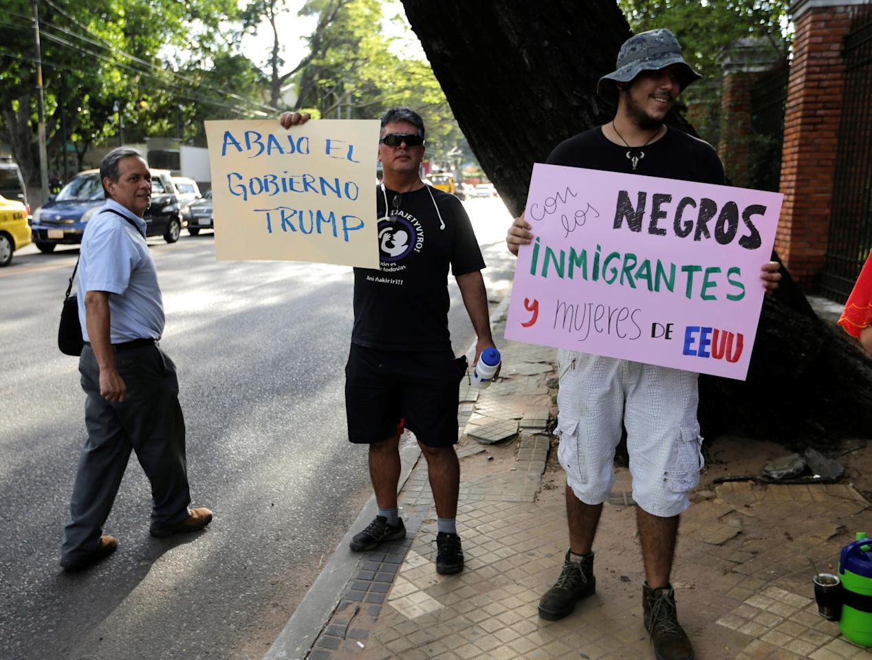 "Protesters hold up signs during a protest against U.S. President Donald Trump outside the United States embassy in Asuncion, Paraguay, January 20, 2017. Signs read ""Down with Trump's Government' and ""We are with the black immigrants and women of the United States"" (R)  REUTERS/Jorge Adorno"