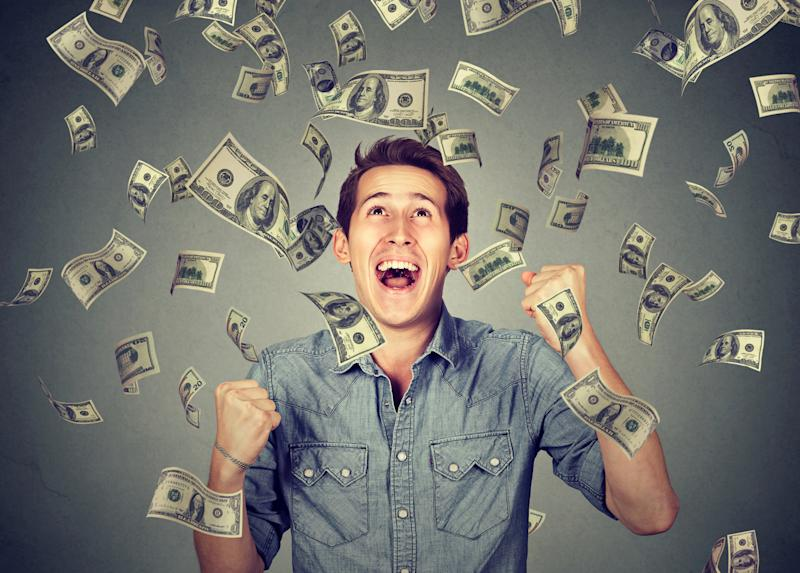 A smiling young man stands in a shower of paper currency