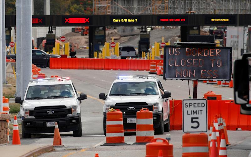 US customs vehicles stand near a sign reading that the border is closed to non-essential traffic, at the Canada-United States border crossing at the Thousand Islands Bridge - Reuters
