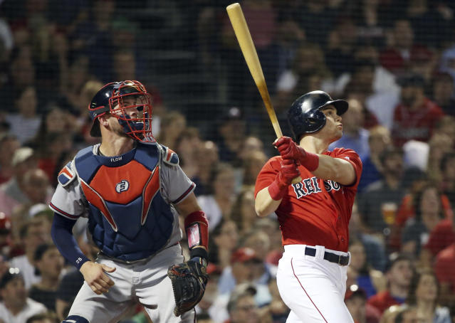 Boston Red Sox's Andrew Benintendi, right, watches his sacrifice fly, scoring Jackie Bradley Jr., in front of Atlanta Braves catcher Tyler Flowers in the fifth inning of an interleague baseball game at Fenway Park, Friday, May 25, 2018, in Boston. (AP Photo/Elise Amendola)