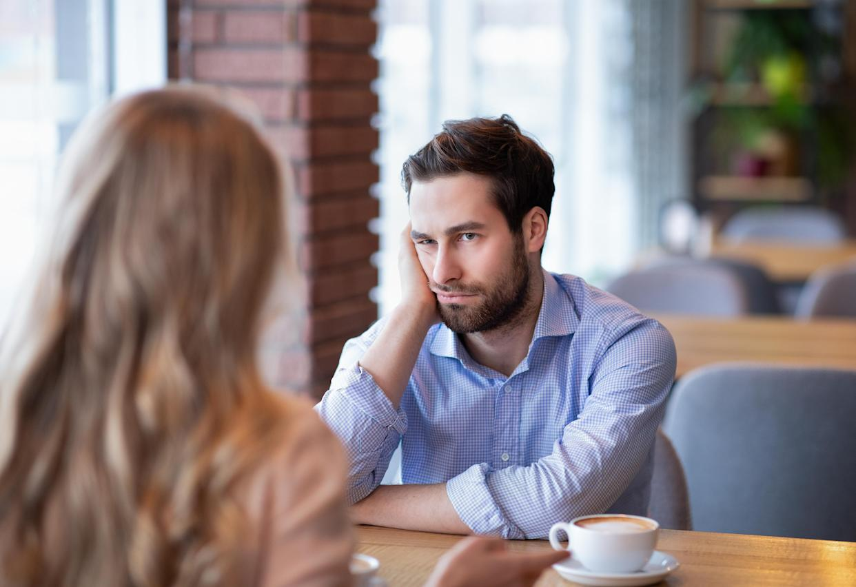 Young guy feeling bored on dull date at restaurant, disappointed in his partner. Millennial couple having disagreement, cannot find common grounds. Relationship problem concept