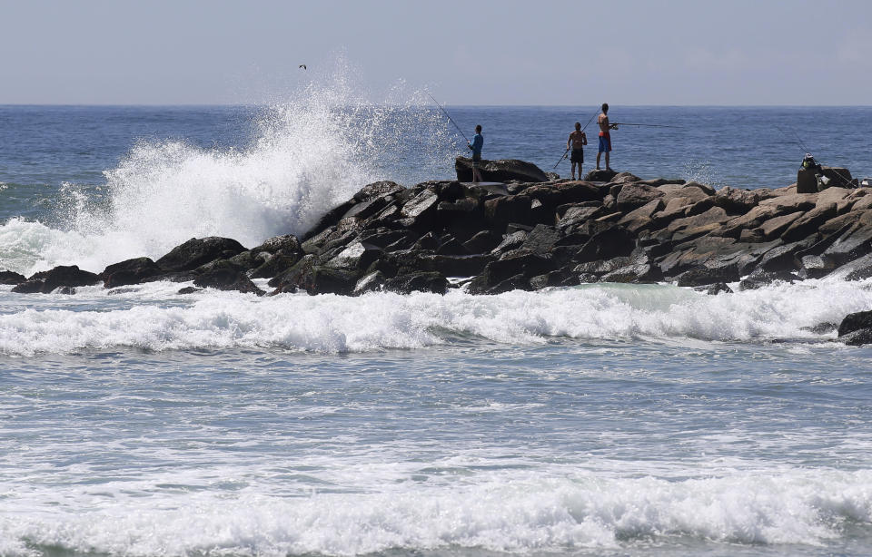 People fish as large waves hit the rocks at the Charlestown Breachway Saturday, Aug. 21, 2021, in Charlestown, R.I. New Englanders, bracing for their first direct hit by a hurricane in 30 years, are taking precautions as Tropical Storm Henri barrels toward the southern New England coast. (AP Photo/Stew Milne)