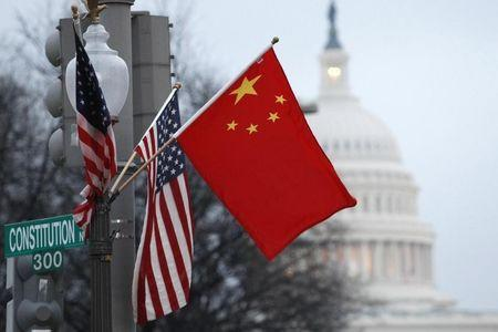 The People's Republic of China flag and the U.S. Stars and Stripes fly on a lamp post along Pennsylvania Avenue near the U.S. Capitol in Washington