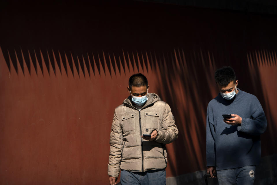 People wearing face masks to protect against the spread of the coronavirus use their smartphones as they walk through Ditan Park in Beijing, Tuesday, Feb. 9, 2021. China's internet watchdog is cracking down further on online speech, issuing a new requirement that bloggers and influencers have a government-approved credential before they can publish on certain topics. (AP Photo/Mark Schiefelbein)