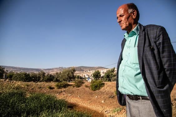 Khaled, 50, a farmer overlooks the dried out pond which once fed his fields (Bel Trew)