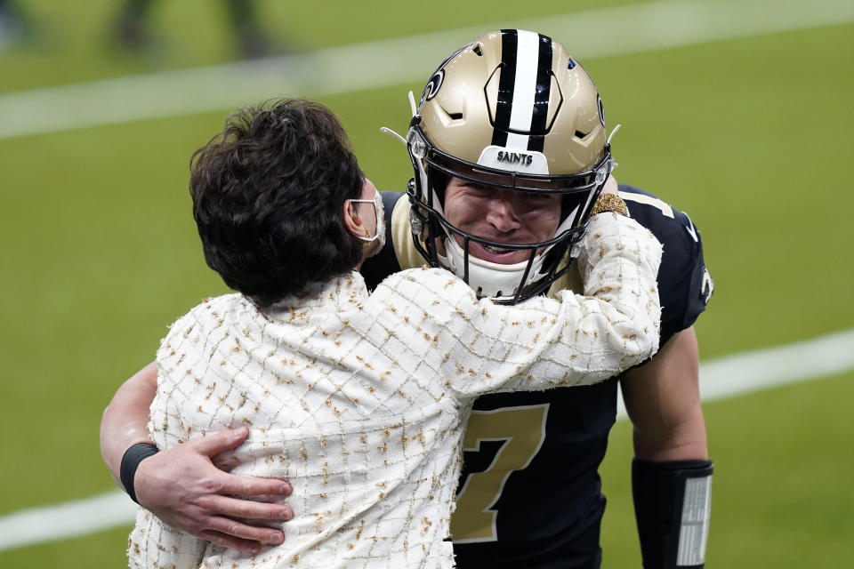 New Orleans Saints quarterback Taysom Hill (7), starting in place of an injured Drew Brees, hugs team owner Gayle Benson before an NFL football game against the Atlanta Falcons in New Orleans, Sunday, Nov. 22, 2020. (AP Photo/Butch Dill)