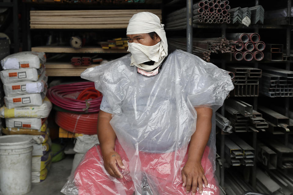 A worker wears an improvised mask to curb the spread of COVID19 and plastic sheet to protect him from rain at the border of the Bulacan province and Caloocan city, Philippines, as they undergo stricter quarantine measures on Monday Aug. 10, 2020. The capital and outlying provinces recently returned to another lockdown after medical groups warned that the country was waging a losing battle against the coronavirus amid an alarming surge in infections. (AP Photo/Aaron Favila)