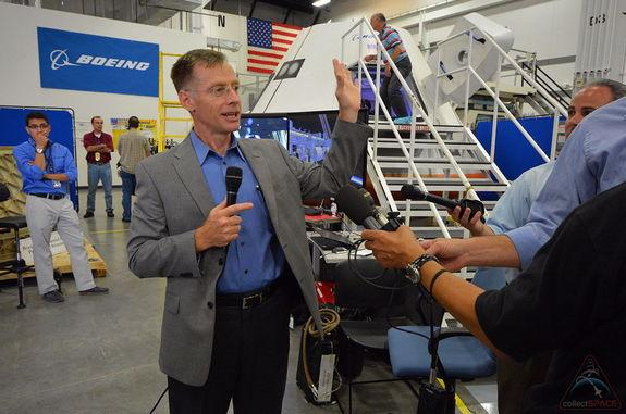 Chris Ferguson, who commanded the final mission of the space shuttle two years ago, talks with media gathered to tour Boeing's CST-100 commercial spacecraft model, July 22, 2013.