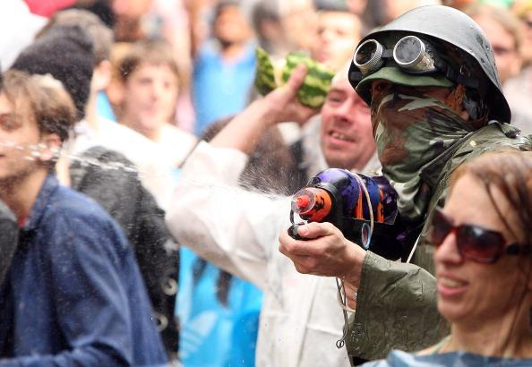 Participants fight in the the annual Vegetable Battle (Gemueseschlacht) on the Oberbaumbruecke on September 2, 2012 in Berlin, Germany. The event pits Kreuzberg district residents againts those of Friedrichshain for control of the Oberbaumbruecke (Oberbaum Bridge), and the two sides pelt each other with rotten vegetables, pet food, ketchup, chicken drumsticks, flour, water guns and styrofoam bats until one side has pushed the other from the bridge. Friedrichshain won the war, in revenge for Kreuzberg's victory the previous year. (Photo by Adam Berry/Getty Images)