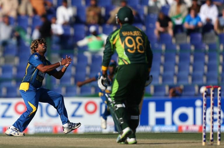 Pakistani batsman Sharjeel Khan (R, foreground) looks on before his imminent dismissal as Sri Lankan bowler Lasith Malinga prepares to catch the ball during the fifth and final One Day International cricket match between Pakistan and Sri Lanka in Abu Dhabi on December 27, 2013.       AFP PHOTO/MARWAN NAAMANI