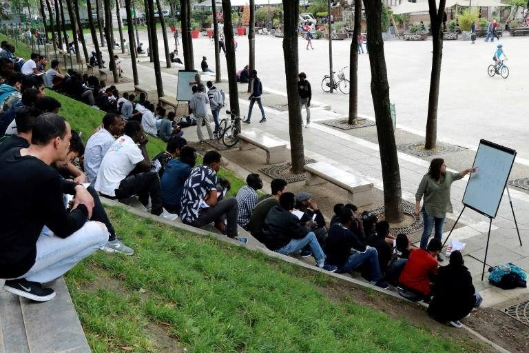 A volunteer delivers a French language class near Place de Stalingrad in Paris for migrants mainly from Sudan and Afghanistan