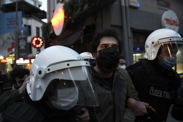 Turkish police officers arrest a youth during clashes with students of the Bogazici University protesting the appointment of a government loyalist to head their university, in Istanbul, Tuesday, Feb. 2, 2021. For weeks, students and faculty at Istanbul's prestigious Bogazici University have been protesting President Recep Tayyip Erdogan's appointment of Melih Bulu, a figure who has links to his ruling party, as the university's rector. They have been calling for Bulu's resignation and for the university to be allowed to elect its own president. (AP Photo/Omer Kuscu)