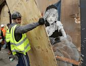 Workmen cover up, for the second time, a new artwork by Banksy, depicting the girl from Les Misérables affected by tear gas, opposite the French embassy in Knightsbridge, London.