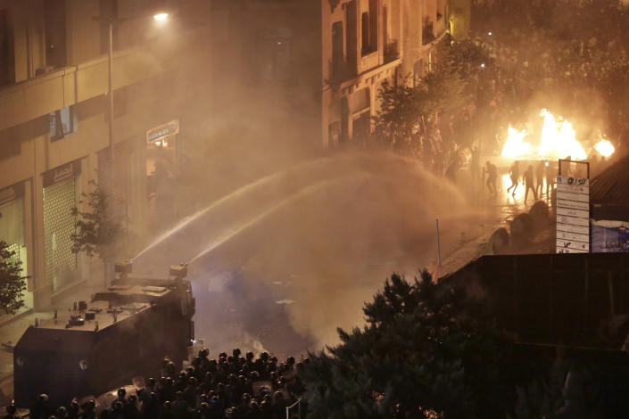Lebanese riot police use water cannon on anti-government protesters during a protest against government's plans to impose new taxes in Beirut, Lebanon, Friday, Oct. 18, 2019. Demonstrators in Lebanon are blocking major roads across the country in a second day of protests against proposed new taxes, which come amid a severe economic crisis. (AP Photo/Hassan Ammar)