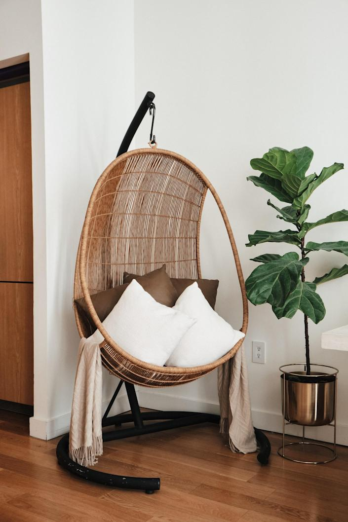 In the corner of Candace's dining area, a hanging hammock chair makes a cozy nook.