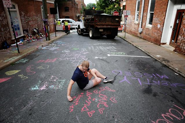 <p>Kim Ganczak writes on the street with chalk near a makeshift memorial for Heather Heyer, who was killed one year ago tomorrow during a deadly clash, Aug. 11, 2018 in Charlottesville, Va. (Photo: Win McNamee/Getty Images) </p>