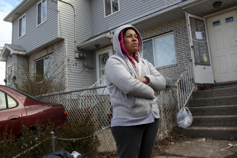 In this Nov. 14, 2012 photo, Mexican immigrant Maria Lucero stands in front of the home she rented which was damaged by Superstorm Sandy in the Midland Beach section of Staten Island, New York.  After the storm, Lucero and her family moved in with friends, but Lucero says it is a temporary situation and will feel more at peace when they have their own home again. Superstorm Sandy has plunged many immigrants living illegally in the United States into darkness, and even deeper into the shadows. Those who desperately need help to get temporary housing assistance and food are afraid to come forward because they risk deportation. And many have ended up returning to damaged, powerless, moldy homes because they have no other place to stay. (AP Photo/Seth Wenig)