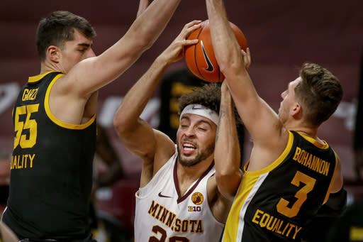 Minnesota guard Gabe Kalscheur (22) finds difficulty getting past Iowa center Luka Garza (55) and guard Jordan Bohannon (3) during the first half of an NCAA college basketball game Friday, Dec. 25, 2020, in Minneapolis. (AP Photo/Bruce Kluckhohn)