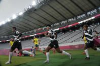 Players from Fiji, front, and Australia jog out to take the field for their women's rugby sevens quarterfinal match at the 2020 Summer Olympics, Friday, July 30, 2021 in Tokyo, Japan. (AP Photo/Shuji Kajiyama)