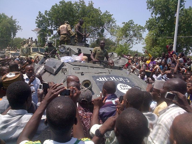 Maiduguri residents welcome troops who recovered an armored personnel carrier (APC) from Boko Haram insurgents in Konduga on September 16, 2014 (AFP Photo/Tunji Omirin)