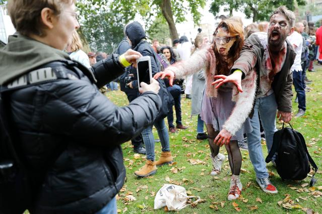 <p>People pose for a photograph before participating in a zombie walk on World Zombie Day in London on Oct. 7, 2017. (Photo: Tolga Akmen/AFP/Getty Images) </p>