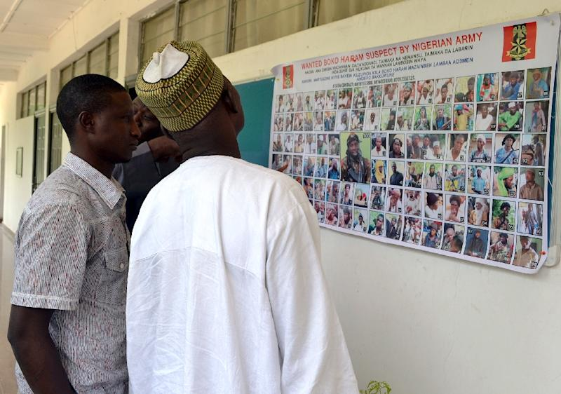 People look at a poster in Maiduguri on October 28, 2015 displaying 100 Boko Haram suspects declared wanted by the Nigerian army