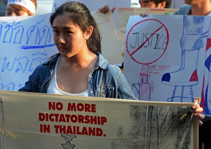 Thai students display placards as they demonstrate in front of the military court in Bangkok on March 16, 2015 (AFP Photo/Pornchai Kittiwongsakul)