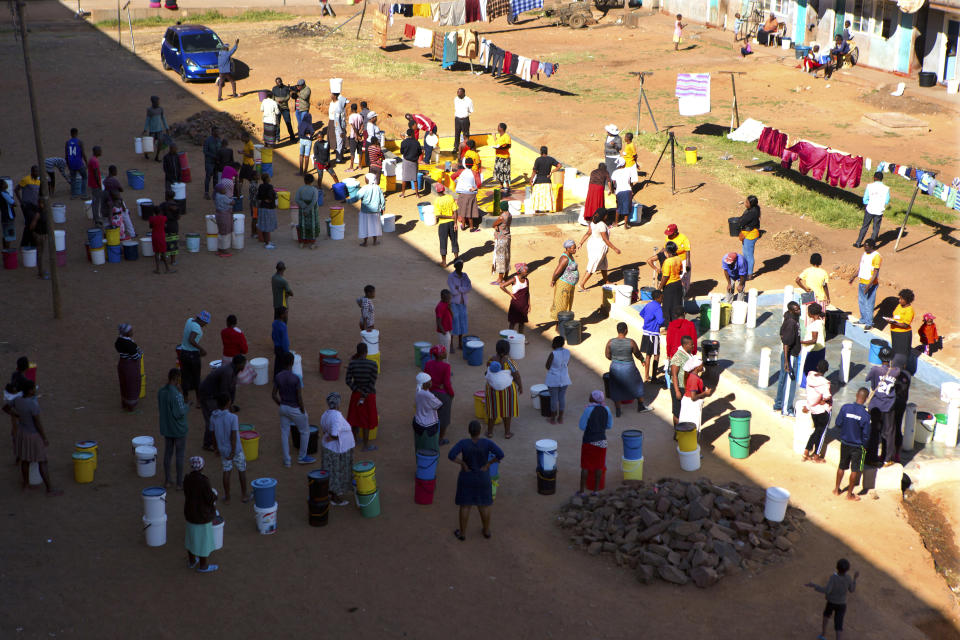 In this April, 24, 2020, photo, people wait to fetch water from a row of communal taps that the group Doctors Without Borders provided in a suburb of Harare, Zimbabwe. For people around the world who are affected by war and poverty, the simple act of washing hands is a luxury. In Zimbabwe, clean water is often saved for daily tasks like doing dishes and flushing toilets. (AP Photo/Tsvangirayi Mukwazhi)