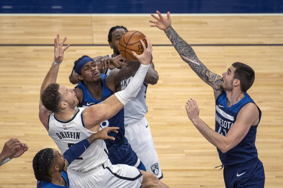 Brooklyn Nets forward Blake Griffin, left, is fouled by Minnesota Timberwolves forward Jarred Vanderbilt, center, as Timberwolves forward Juancho Hernangomez, right, tries to block his shot during the first half of an NBA basketball game Tuesday, April 13, 2021, in Minneapolis. (AP Photo/Craig Lassig)