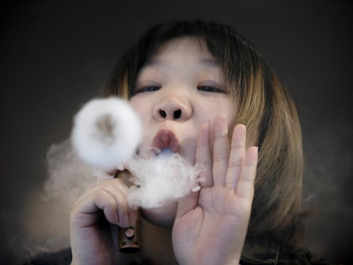 FILE PHOTO: A saleswoman demonstrates vaping at the Vape Shop that sells e-cigarette products in Beijing, China January 30, 2019. REUTERS/Thomas Peter