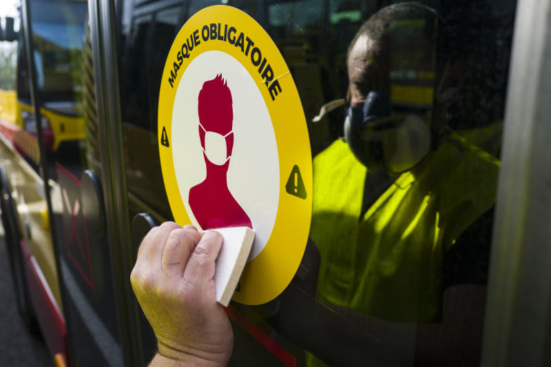 A man places a sticker reading 'Mandatory Masks' on a School bus door in Mulhouse, eastern France, on May 8, 2020, as France readies for May 11, easing of the lockdown which began on March 17, to stop the spread of the Covid-19 pandemic caused by the novel coronavirus. - France is scheduled May 11, to start easing a lockdown that began in mid-March as the number of cases, hospitalisations and deaths show signs of slowing. (Photo by SEBASTIEN BOZON / AFP) (Photo by SEBASTIEN BOZON/AFP via Getty Images)