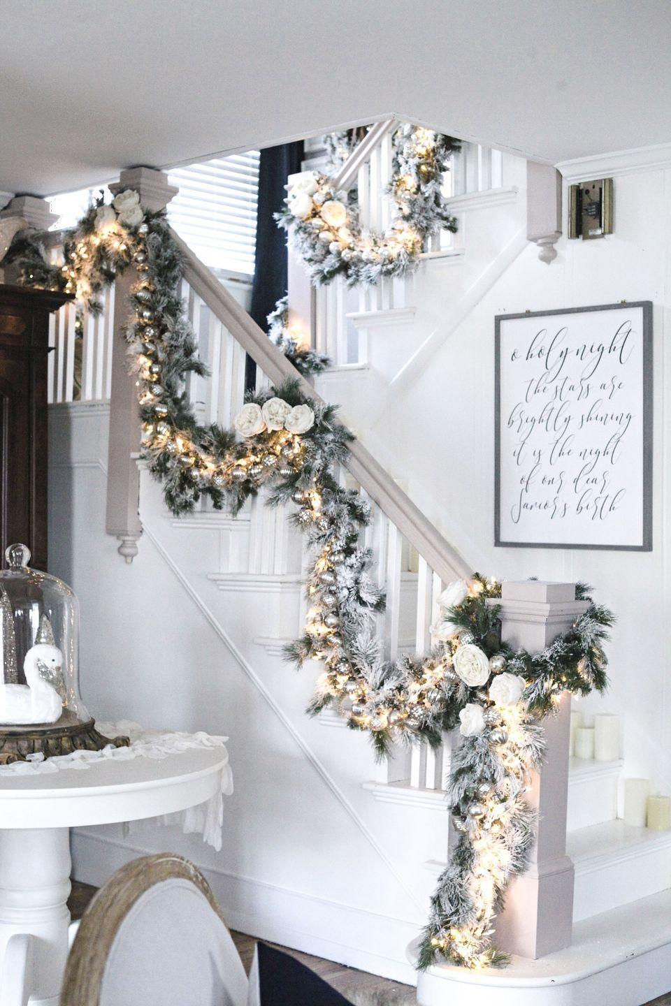 """<p>Frosty holiday stair decor assembled by Tammy Damore of <a href=""""http://tammydamore.com/"""" rel=""""nofollow noopener"""" target=""""_blank"""" data-ylk=""""slk:The Cultivated Home"""" class=""""link rapid-noclick-resp"""">The Cultivated Home</a> has us dreaming of a white Christmas, with snow-dusted garland and white roses. </p>"""