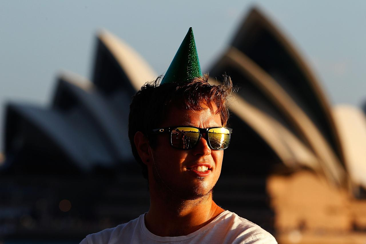 SYDNEY, AUSTRALIA - DECEMBER 31:  A man wearing a party hat waits in anticipation of New Years Eve celebrations on Sydney Harbour on December 31, 2012 in Sydney, Australia.  (Photo by Brendon Thorne/Getty Images)
