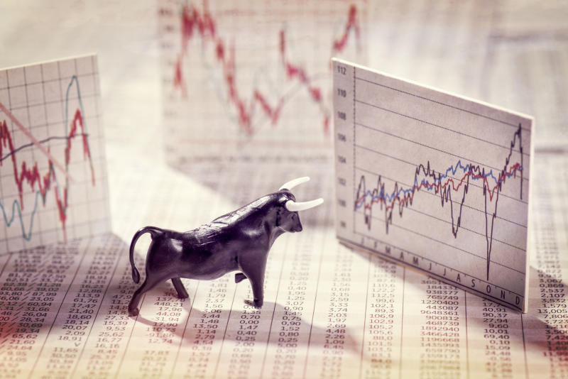 Small black bull figurine next to multiple paper stock market charts and figures.