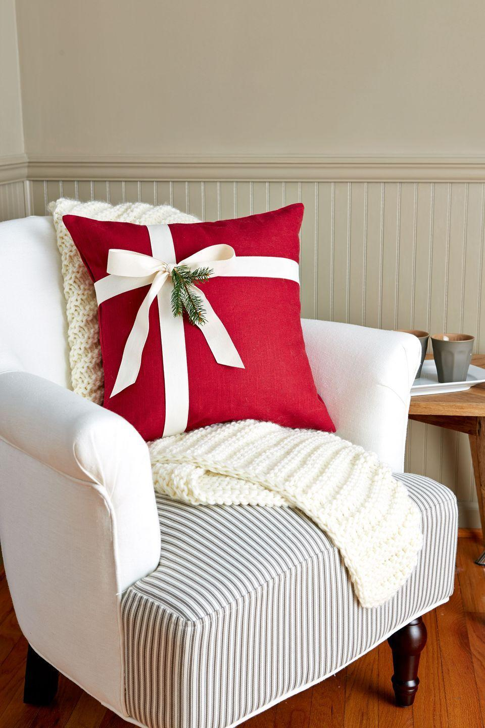 """<p>Take a plain <a href=""""https://www.amazon.com/Decorative-Cushion-Pillow-Sleeve-Percent/dp/B019CSMYYA/?tag=syn-yahoo-20&ascsubtag=%5Bartid%7C10050.g.645%5Bsrc%7Cyahoo-us"""" rel=""""nofollow noopener"""" target=""""_blank"""" data-ylk=""""slk:pillow"""" class=""""link rapid-noclick-resp"""">pillow</a> from ho-hum to ho-ho-ho by simply wrapping it like a present. (Yes, it's that simple.) Add a sprig of greenery or a festive ornament for an extra bit of flourish.</p><p><strong><a class=""""link rapid-noclick-resp"""" href=""""https://www.amazon.com/Decorative-Cushion-Pillow-Sleeve-Percent/dp/B019CSMYYA/?tag=syn-yahoo-20&ascsubtag=%5Bartid%7C10050.g.645%5Bsrc%7Cyahoo-us"""" rel=""""nofollow noopener"""" target=""""_blank"""" data-ylk=""""slk:SHOP PILLOWS"""">SHOP PILLOWS</a></strong></p>"""