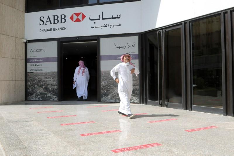 Saudi men are seen at SABB bank as the government eases lockdown restrictions amid the coronavirus disease (COVID-19) outbreak, in Riyadh
