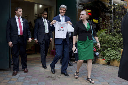 """U.S. Secretary of State John Kerry holds """"I love Cambodia"""" t-shirt that he bought for his grandchild as he walks out of the souvenir shop in Phnom Penh, Cambodia, January 26, 2016. REUTERS/Jacquelyn Martin/Pool"""