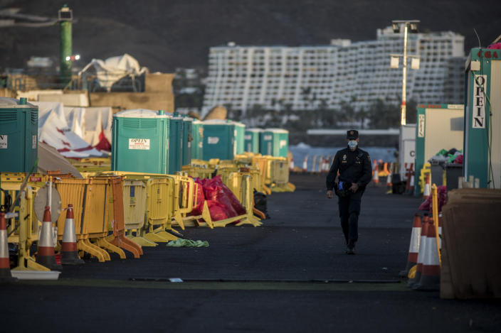 """A police officer walks along the empty makeshift migrant camp located at Arguineguin port on the southwestern coast of the Gran Canaria island, Spain on Monday Nov. 30, 2020. Spain has dismantled most of the temporary camp for migrant processing that for over three months became known as the """"dock of shame"""" for holding in unfit conditions thousands of Africans arriving lately in the Canary Islands. (AP Photo/Javier Fergo)"""
