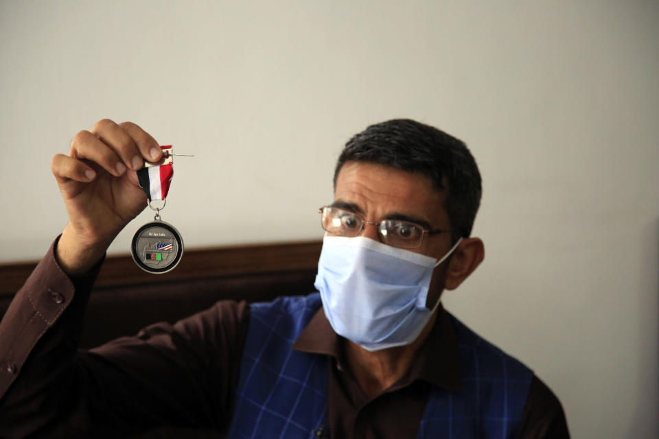In this Friday, April 30, 2021, photo Ayazudin Hilal, 40, a former Afghan interpreter for the U.S. hold his medal during an interview to The Associated Press after a protest against the U.S. government and NATO in Kabul, Afghanistan. (AP Photo/Mariam Zuhaib)